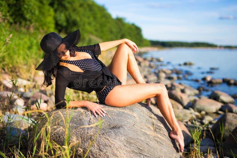 Νέα όμορφη γυναίκα στην τοποθέτηση μπικινιών στη δύσκολη παραλία στοκ φωτογραφία