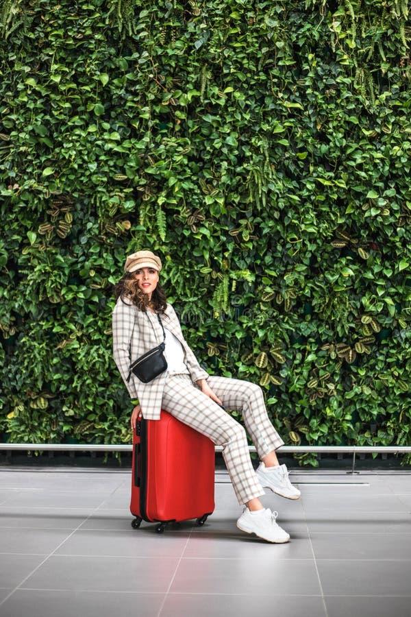 Νέα όμορφη γυναίκα στον αερολιμένα ενάντια στον πράσινο τοίχο στοκ φωτογραφίες