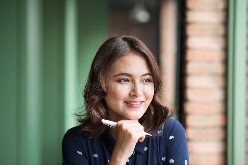 Νέα όμορφη γυναίκα στον καφέ κοντά στο παράθυρο, που σκέφτεται και που γράφει κάτι στοκ φωτογραφία με δικαίωμα ελεύθερης χρήσης