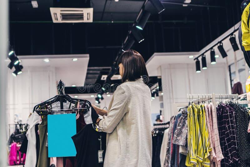 Νέα όμορφη γυναίκα στο κατάστημα μόδας E στοκ εικόνες