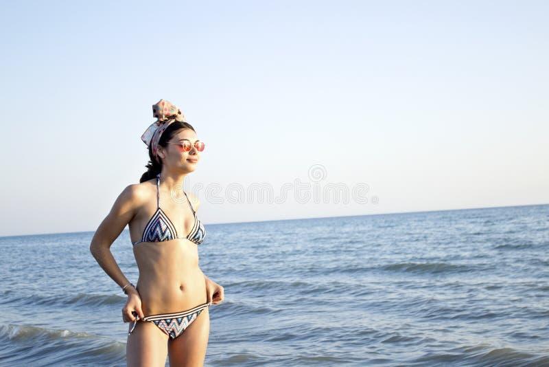 Νέα όμορφη γυναίκα στο μαγιό που στέκεται στην παραλία στοκ εικόνες