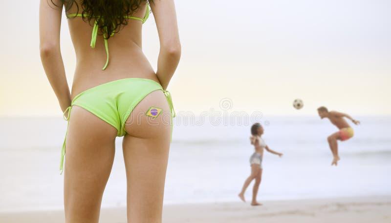 Νέα όμορφη γυναίκα στο μπικίνι στο παιχνίδι ζευγών προσοχής παραλιών με το ποδόσφαιρο στοκ εικόνες