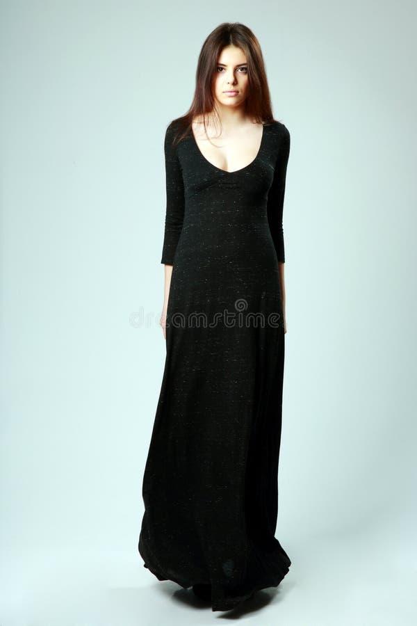 Νέα όμορφη γυναίκα στο πολύ μαύρο φόρεμα στοκ φωτογραφία