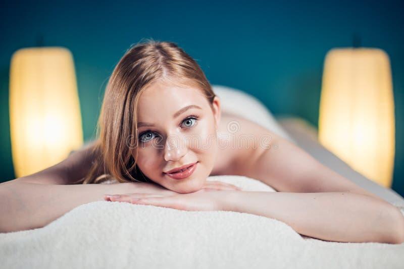 Νέα, όμορφη γυναίκα στο σαλόνι SPA που βρίσκεται στον πίνακα μασάζ που περιμένει το μασάζ στοκ εικόνες