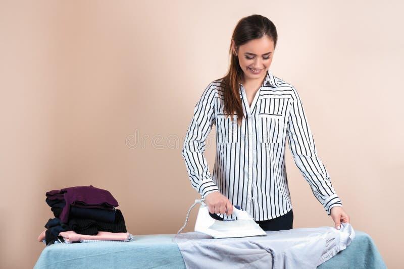 Νέα όμορφη γυναίκα στο σιδέρωμα πουκάμισων, μητέρα νοικοκυρών που χρησιμοποιεί το σίδηρο στοκ φωτογραφίες με δικαίωμα ελεύθερης χρήσης