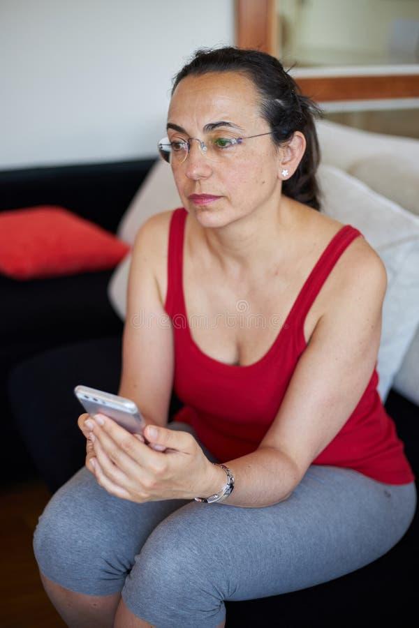 Νέα όμορφη γυναίκα στο σπίτι με το έξυπνο τηλέφωνο κινητό στοκ φωτογραφία με δικαίωμα ελεύθερης χρήσης