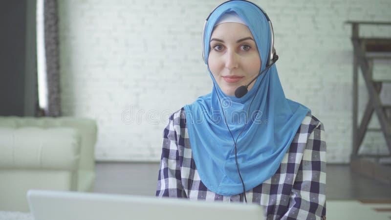 Νέα όμορφη γυναίκα στο hijab με τα ακουστικά και την κάσκα, εργαζόμενος τηλεφωνικών κέντρων στοκ εικόνες με δικαίωμα ελεύθερης χρήσης