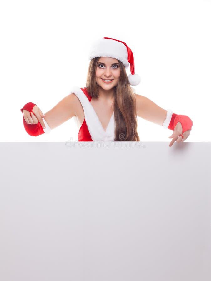 Νέα όμορφη γυναίκα Χριστουγέννων στο καπέλο santa που κρατά τον κενό πίνακα στοκ εικόνες
