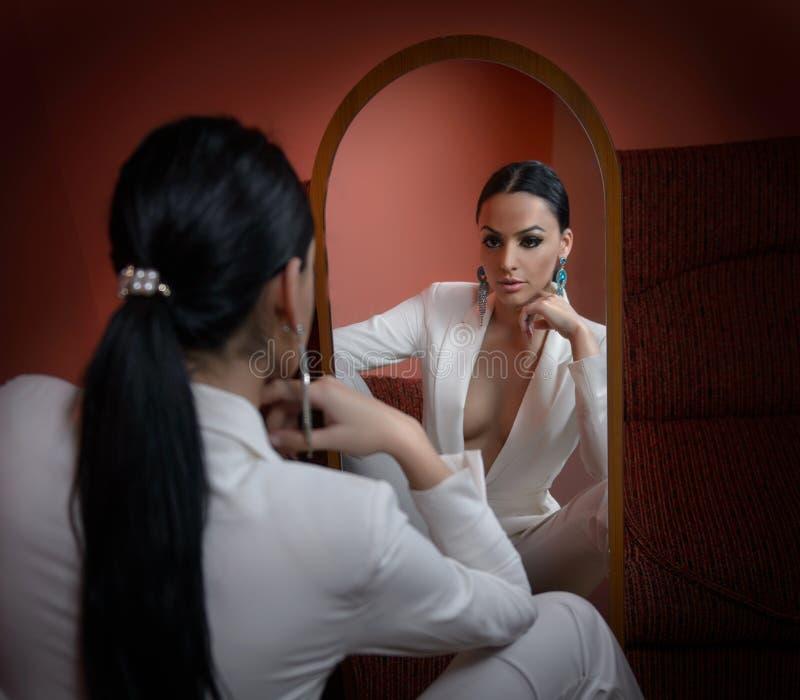 Νέα όμορφη γυναίκα brunette στο κομψό άσπρο κοστούμι με το παντελόνι που εξετάζει το μεγάλο καθρέφτη Σαγηνευτική σκοτεινή τοποθέτ στοκ φωτογραφίες με δικαίωμα ελεύθερης χρήσης