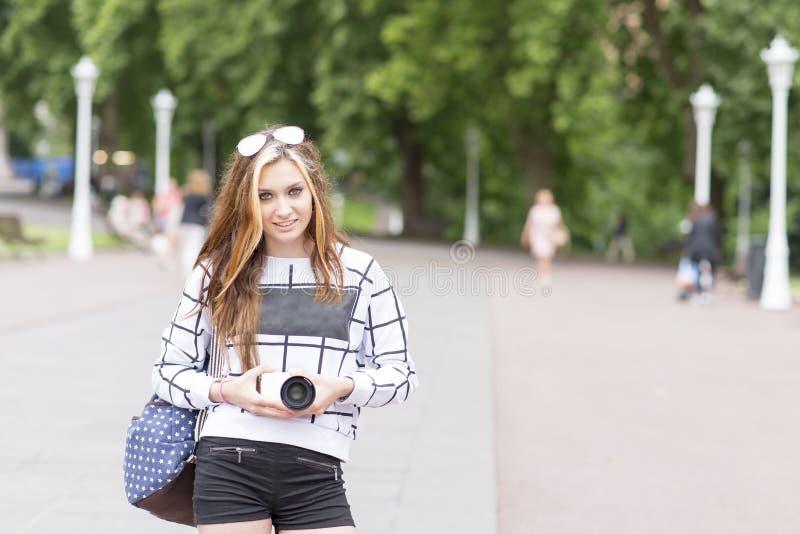 Νέα όμορφη γυναίκα hipster με τη ψηφιακή κάμερα στην οδό στοκ εικόνες
