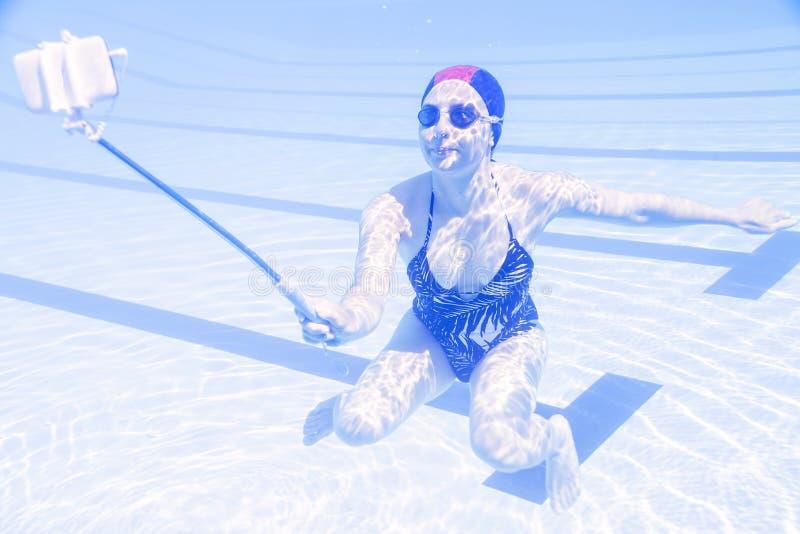 Νέα όμορφη γυναίκα tekes ένα selfie υποβρύχιο στοκ εικόνα