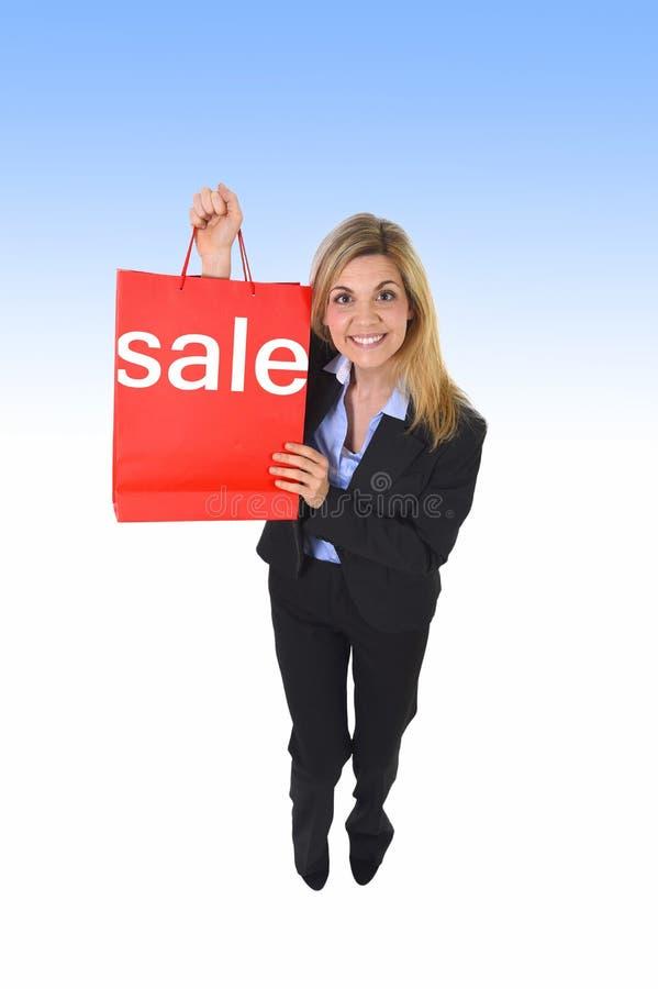 Νέα όμορφη γυναικών εκμετάλλευσης τσάντα αγορών πώλησης κόκκινη στοκ εικόνα