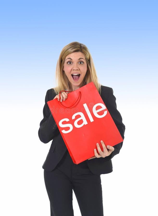 Νέα όμορφη γυναικών εκμετάλλευσης τσάντα αγορών πώλησης κόκκινη στοκ εικόνες