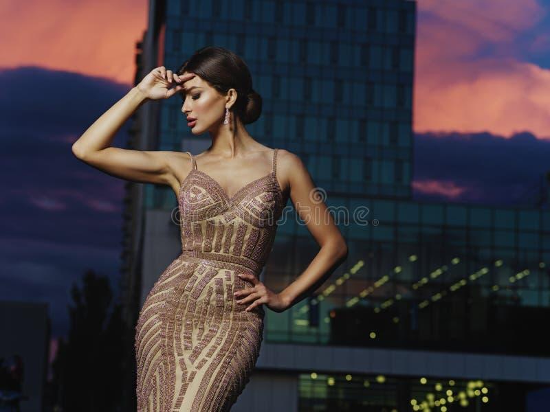 Νέα όμορφη επιδέξια ντυμένη κομψή γυναίκα με το makeup και hairstyle στο εκφραστικό λαμπιρίζοντας φόρεμα βραδιού στοκ εικόνες