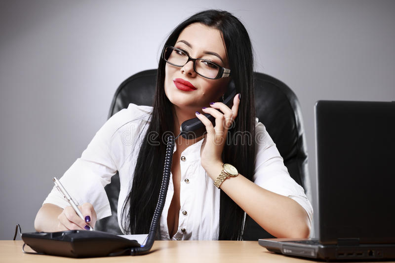 νέα όμορφη επιχειρησιακή γυναίκα που εργάζεται στο γραφείο της στοκ φωτογραφία