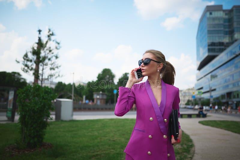 Νέα όμορφη επιχειρησιακή γυναίκα που μιλά στο τηλέφωνο E στοκ φωτογραφίες