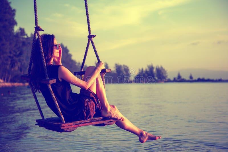 Νέα όμορφη ευτυχής γυναίκα που ταλαντεύεται σε μια ταλάντευση στην παραλία κατά τη διάρκεια του ηλιοβασιλέματος, χαλαρώνοντας ένν στοκ φωτογραφία