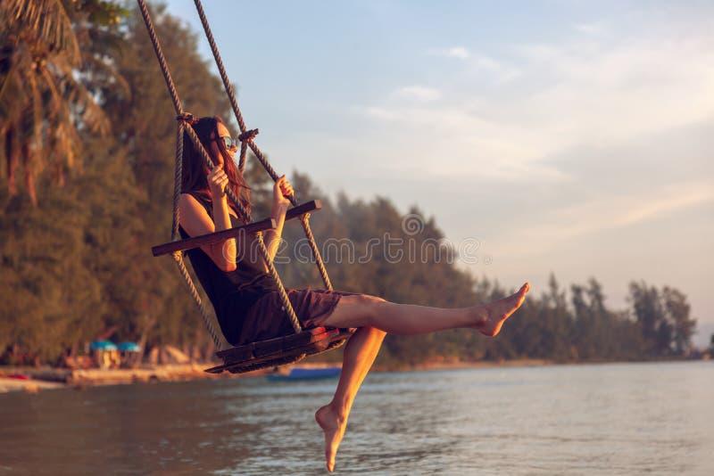 Νέα όμορφη ευτυχής γυναίκα που ταλαντεύεται σε μια ταλάντευση στην παραλία κατά τη διάρκεια του ηλιοβασιλέματος, χαλαρώνοντας ένν στοκ εικόνα