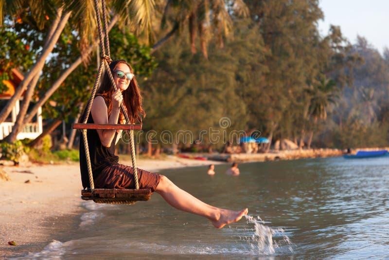Νέα όμορφη ευτυχής γυναίκα που ταλαντεύεται σε μια ταλάντευση στην παραλία κατά τη διάρκεια του ηλιοβασιλέματος, χαλαρώνοντας ένν στοκ φωτογραφίες με δικαίωμα ελεύθερης χρήσης