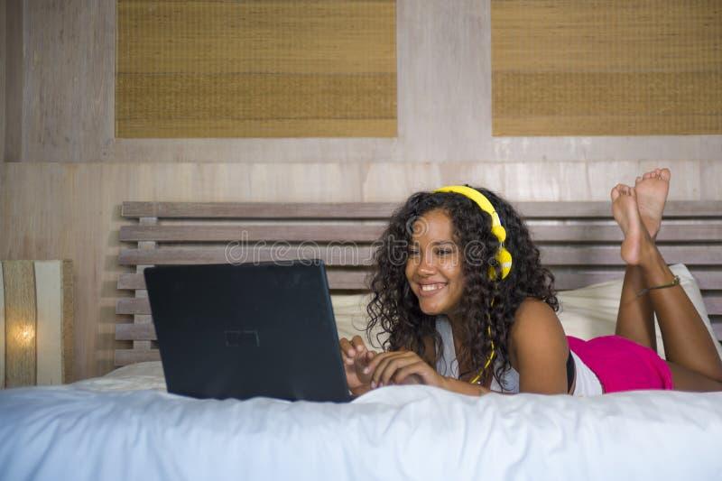Νέα όμορφη ευτυχής μαύρη κρεβατοκάμαρα γυναικών Afro αμερικανική στο σπίτι που βρίσκεται εύθυμη στο κρεβάτι που ακούει τη μουσική στοκ εικόνες