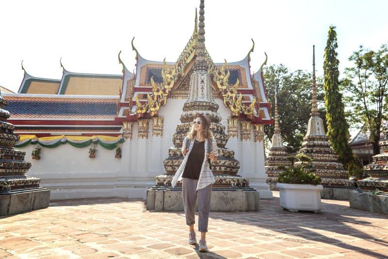 Νέα όμορφη ευτυχής χαμογελώντας Ευρωπαία γυναίκα τουριστών σε ένα καπέλο και γυαλιά σε έναν βουδιστικό ναό στη Μπανγκόκ ταξιδεύω  στοκ εικόνα
