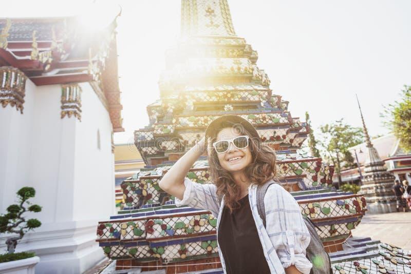 Νέα όμορφη ευτυχής χαμογελώντας Ευρωπαία γυναίκα τουριστών σε ένα καπέλο και γυαλιά σε έναν βουδιστικό ναό στη Μπανγκόκ ταξιδεύω  στοκ φωτογραφία με δικαίωμα ελεύθερης χρήσης