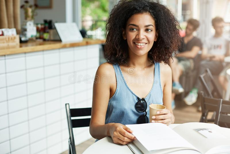 Νέα όμορφη εύθυμη αφρικανική συνεδρίαση γέλιου χαμόγελου σπουδαστών κοριτσιών στον καφέ Περιοδικά βιβλίων που βρίσκονται στον πίν στοκ εικόνα με δικαίωμα ελεύθερης χρήσης