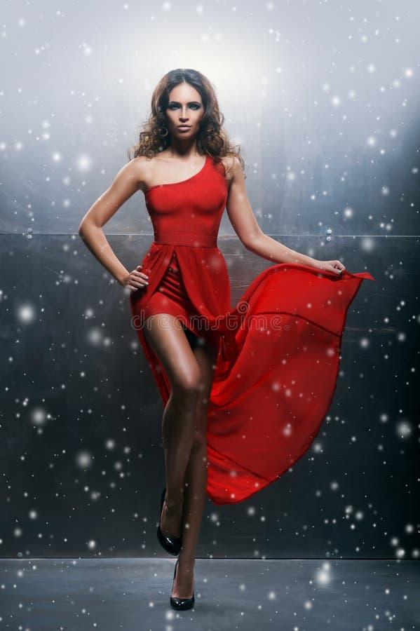 Νέα, όμορφη και εμπαθής γυναίκα σε ένα κυματιστό, μακρύ, κόκκινο φόρεμα στοκ φωτογραφίες
