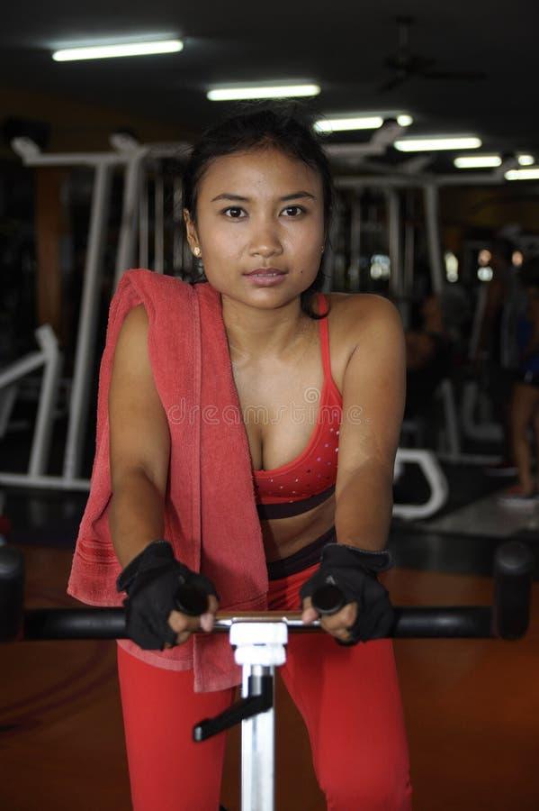 Νέα όμορφη και ιδρωμένη ασιατική ενεργός γυναίκα που εκπαιδεύει σκληρά να ανακυκλώσει και που οδηγά στο στατικό ποδήλατο workout  στοκ εικόνες