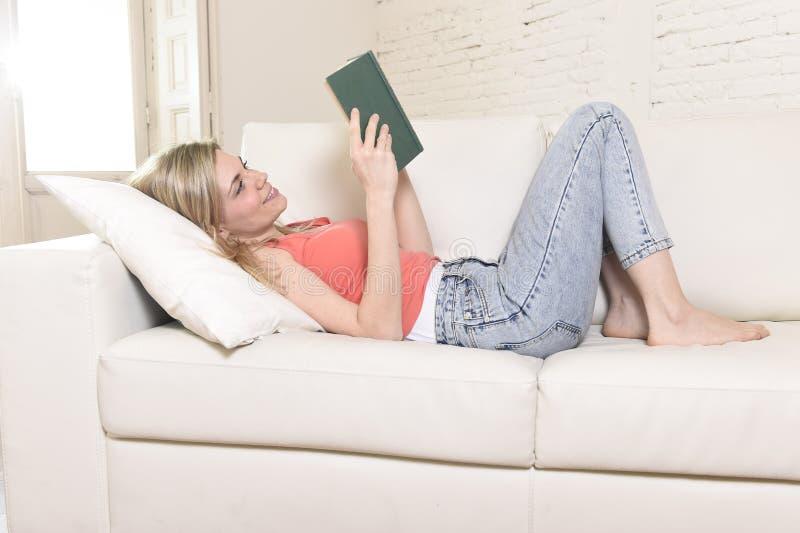 Νέα όμορφη καυκάσια μελέτη βιβλίων ανάγνωσης γυναικών που βρίσκεται άνετη στον εγχώριο καναπέ που φαίνεται ευτυχή στοκ φωτογραφία