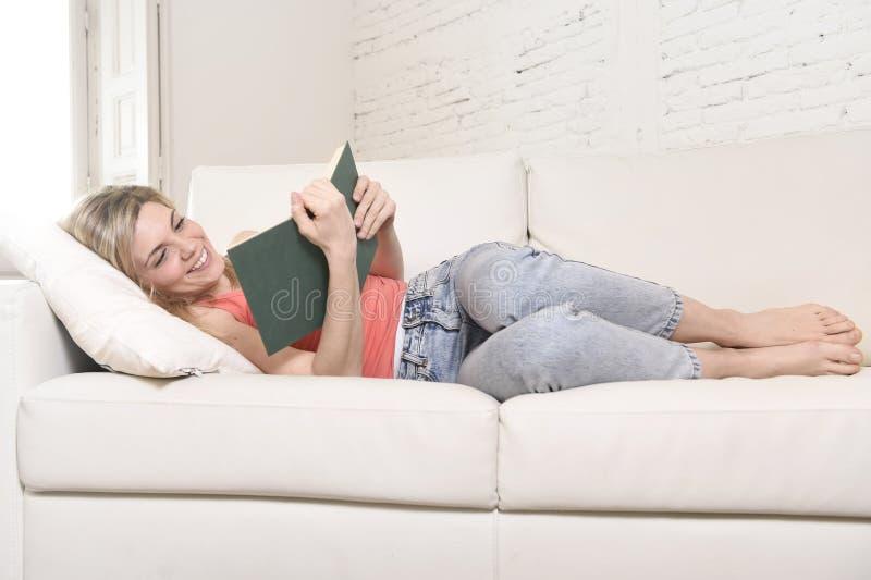 Νέα όμορφη καυκάσια μελέτη βιβλίων ανάγνωσης γυναικών που βρίσκεται άνετη στον εγχώριο καναπέ που φαίνεται ευτυχή στοκ εικόνες