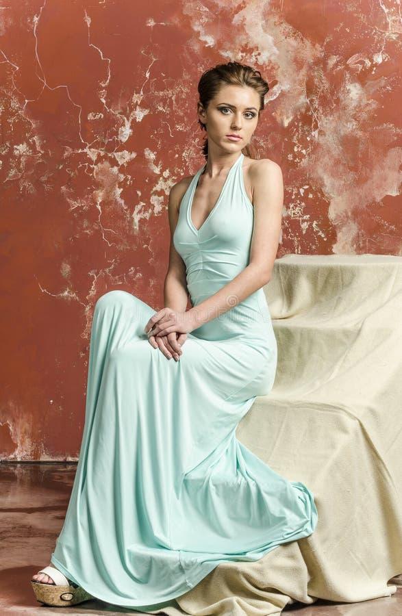 Νέα όμορφη καφετής-μαλλιαρή γυναίκα στο μπλε ελαφρύ φόρεμα μεταξιού με τους ανοικτούς ώμους και μια μακριά φούστα και τα σανδάλια στοκ εικόνες