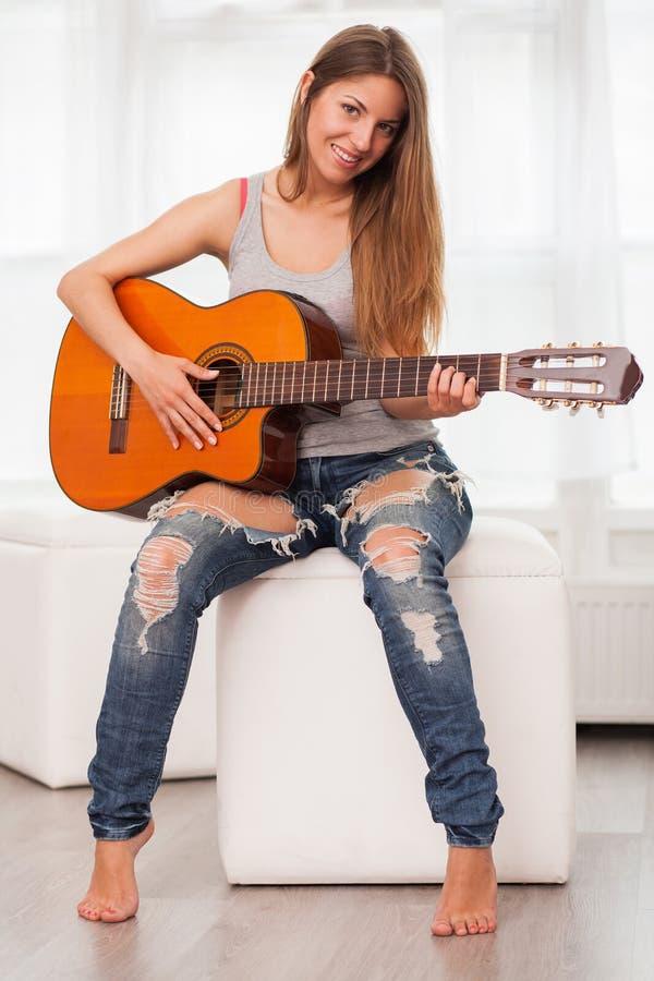 Νέα όμορφη κιθάρα παιχνιδιού γυναικών στοκ φωτογραφίες με δικαίωμα ελεύθερης χρήσης