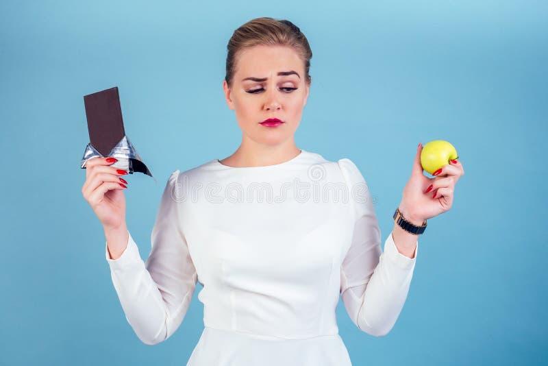 Νέα όμορφη κοπέλα με λευκά μπλουζάκια και επιλογή σοκολάτας ή μήλου Απομονωμένο μπλε πορτραίτο φόντου στο στούντιο στοκ εικόνες