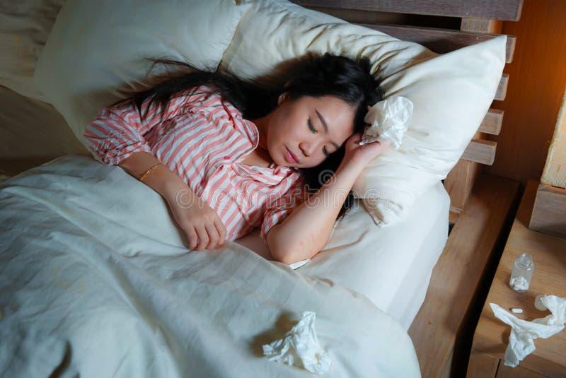 Νέα όμορφη κουρασμένη και άρρωστη ασιατική ιαπωνική γυναίκα που βρίσκεται άρρωστη στο κρεβάτι στις πυτζάμες τη νύχτα με τα έγγραφ στοκ φωτογραφίες