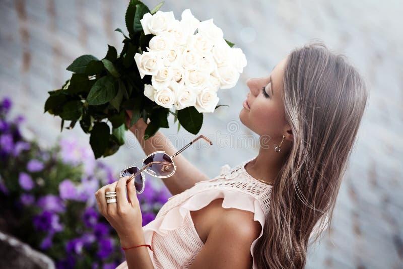 Νέα όμορφη κυρία με μια ανθοδέσμη των τριαντάφυλλων στοκ εικόνα με δικαίωμα ελεύθερης χρήσης
