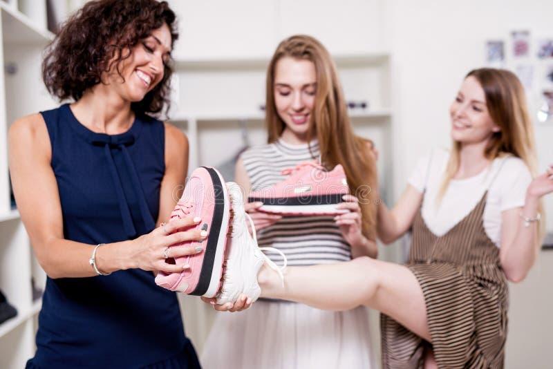 Νέα όμορφη κυρία που στέκεται σε ένα πόδι ενώ ο φίλος της που ελέγχει το νέο μέγεθος υποδημάτων που συγκρίνει το με το παλαιό πέλ στοκ εικόνες με δικαίωμα ελεύθερης χρήσης