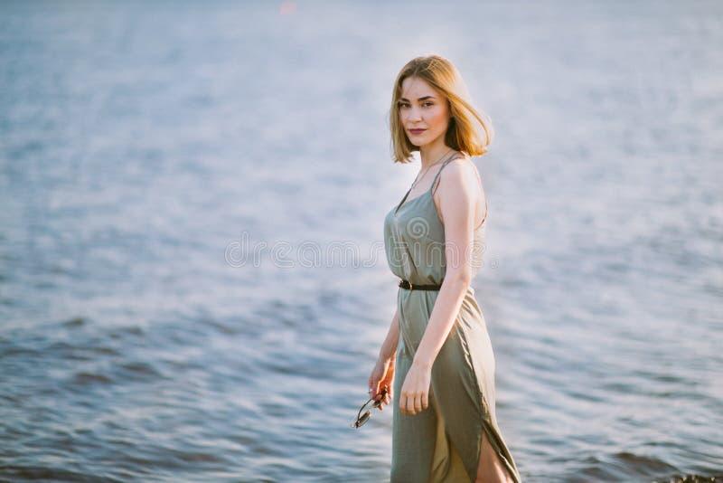Νέα όμορφη λεπτή γυναίκα με την κοντή ελαφριά τρίχα που φορά την πράσινη εν πλω ακτή περπατήματος θερινών φορεμάτων στο ηλιοβασίλ στοκ εικόνα
