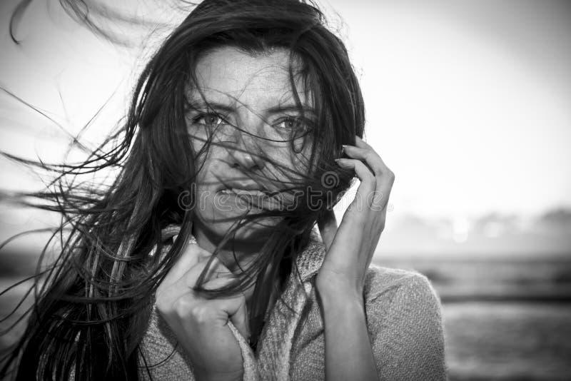 Νέα όμορφη μακρυμάλλης γυναίκα στη θυελλώδη ακτή στοκ φωτογραφία με δικαίωμα ελεύθερης χρήσης