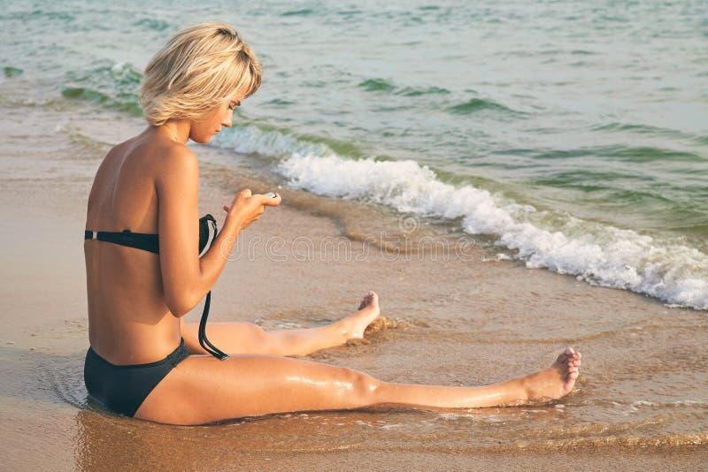Νέα όμορφη μαυρισμένη γυναίκα στο μπικίνι με το κινητό τηλέφωνο σε μια παραλία στοκ φωτογραφία