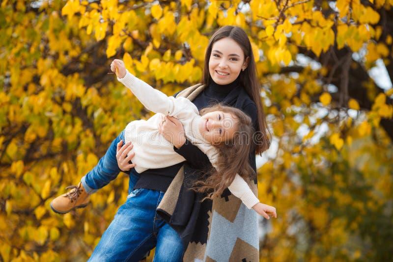 Νέα όμορφη μητέρα με την λίγη κόρη στο πάρκο φθινοπώρου στοκ εικόνες