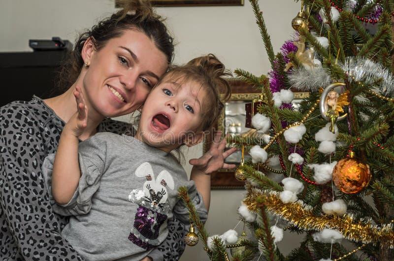 Νέα όμορφη μητέρα με το γοητευτικό φόρεμα κορών της επάνω στα παιχνίδια και το χριστουγεννιάτικο δέντρο γιρλαντών που συντηρεί τι στοκ φωτογραφίες με δικαίωμα ελεύθερης χρήσης