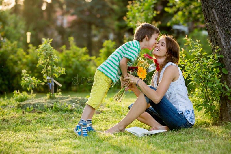 Νέα όμορφη μητέρα, που κάθεται σε έναν κήπο, μικρό παιδί, ο γιος της στοκ φωτογραφία με δικαίωμα ελεύθερης χρήσης