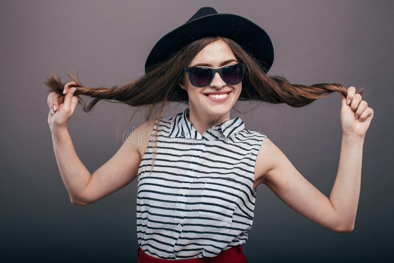 Νέα όμορφη μοντέρνη γυναίκα με το καθιερώνον τη μόδα makeup στο μαύρο καπέλο και γυαλιά στο γκρίζο υπόβαθρο Πρότυπη εξέταση τη κά στοκ φωτογραφίες