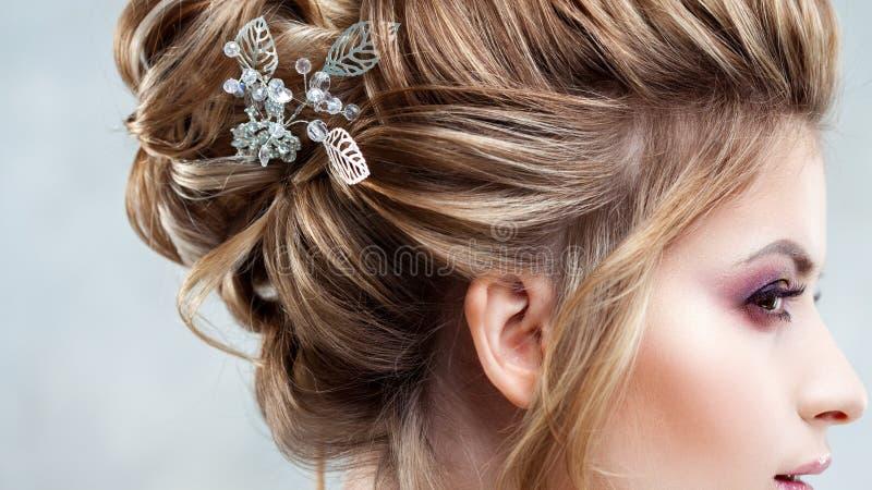 Νέα όμορφη νύφη με ένα κομψό υψηλό hairdo Γάμος hairstyle με το εξάρτημα στην τρίχα της στοκ φωτογραφία