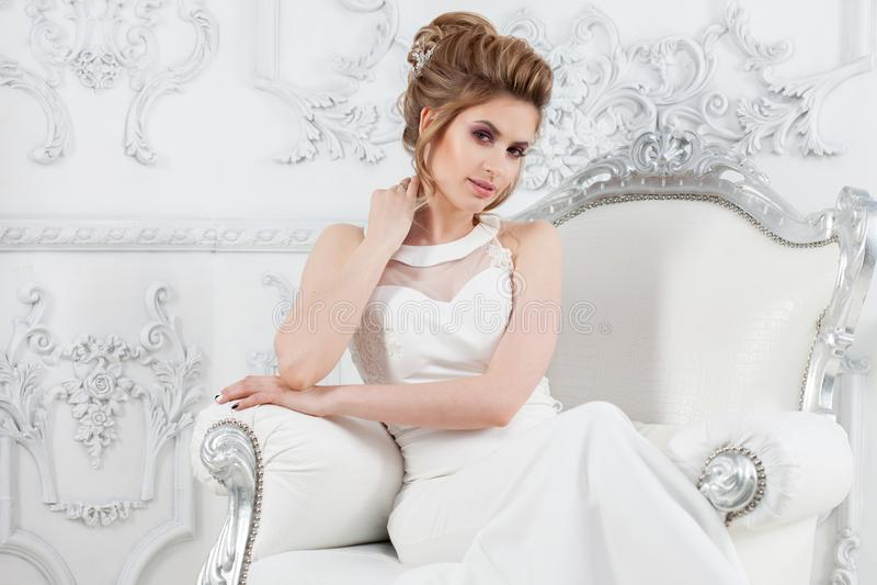 Νέα όμορφη νύφη με ένα κομψό υψηλό hairdo Κομψή νύφη στο πολυτελές εσωτερικό, που κάθεται σε μια καρέκλα στοκ εικόνα με δικαίωμα ελεύθερης χρήσης