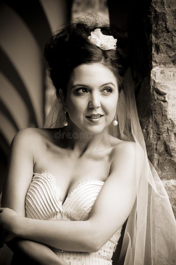 Νέα όμορφη νύφη που κλίνει ενάντια στο στυλοβάτη πετρών στοκ εικόνα με δικαίωμα ελεύθερης χρήσης