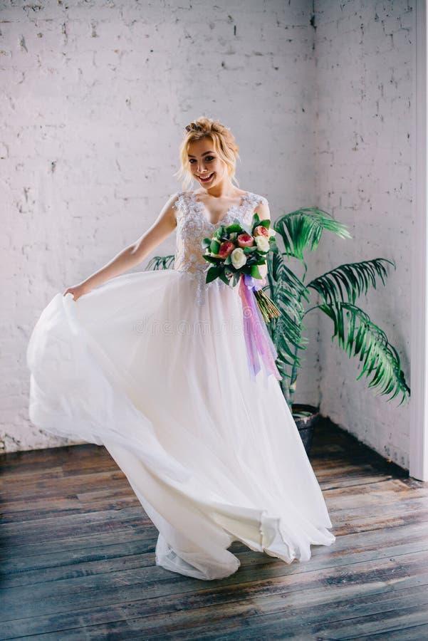 Νέα όμορφη νύφη που χαμογελά και που περιστρέφει στη σοφίτα στοκ εικόνα