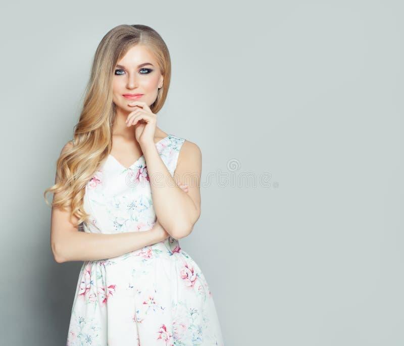 Νέα όμορφη ξανθή γυναίκα που σκέφτεται στο άσπρο κλίμα τοίχων με το διάστημα αντιγράφων στοκ φωτογραφία με δικαίωμα ελεύθερης χρήσης