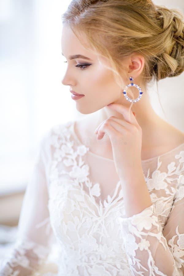 Νέα όμορφη ξανθή τοποθέτηση γυναικών σε ένα γαμήλιο φόρεμα στοκ φωτογραφία